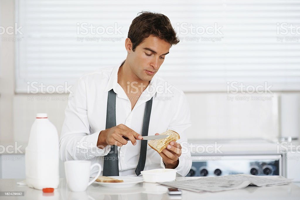 Businessman at home spreading butter on toast royalty-free stock photo