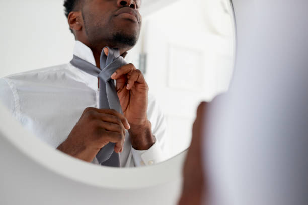 businessman at home tying necktie in mirror before leaving for work - tied up stock pictures, royalty-free photos & images