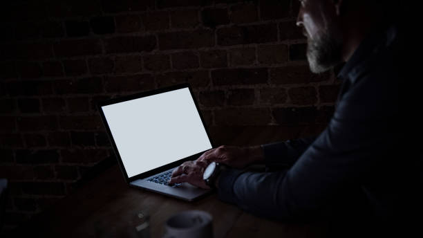 Businessman at laptop with light reflection