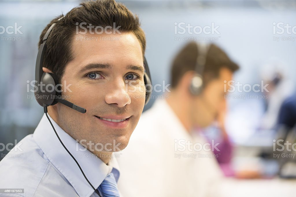 Businessman at office on the phone with headset, looking camera stock photo