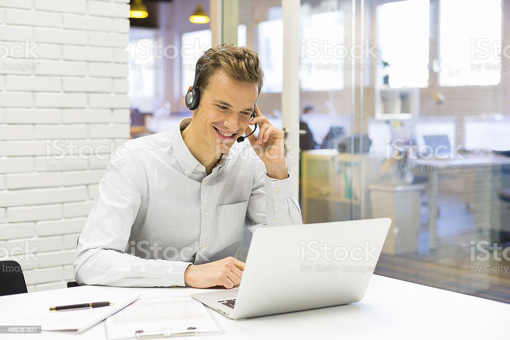 Businessman at office on the phone with headset stock photo
