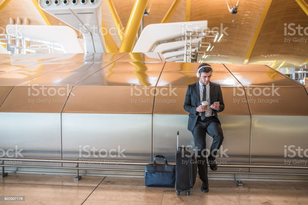 businessman at the airport listening music using his mobile phone waiting his flight stock photo