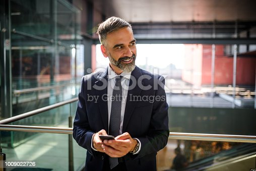 Handsome businessman text messaging on the mobile phone at the airport