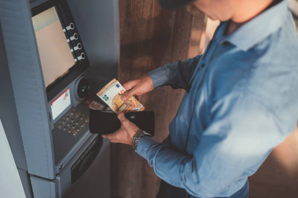 Businessman at the ATM withdrawing money, fifty euro banknotes Close up of businessman withdrawing money and putting in the wallet euro symbol stock pictures, royalty-free photos & images