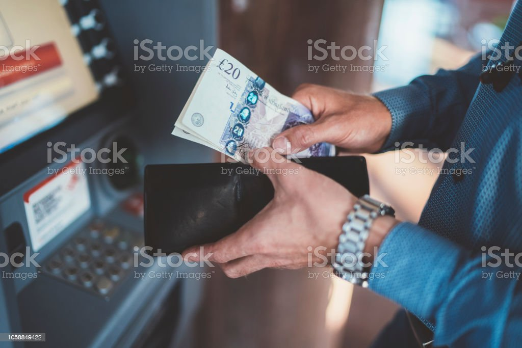 Businessman at the ATM withdrawing money Close up of businessman withdrawing money and putting into wallet ATM Stock Photo