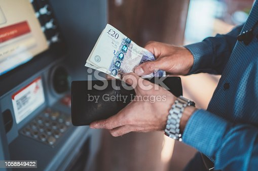 Close up of businessman withdrawing money and putting into wallet
