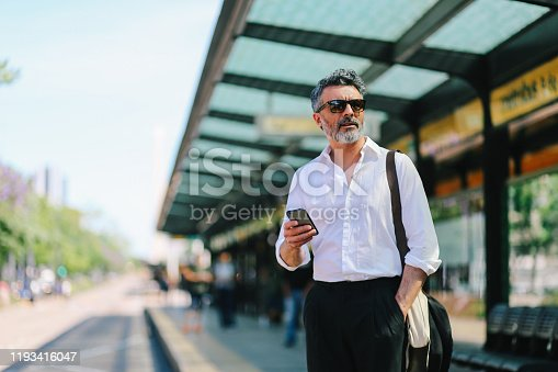 Mature businessman standing and waiting for the train on the Buenos Aires subway station, wearing smart casual clothing.