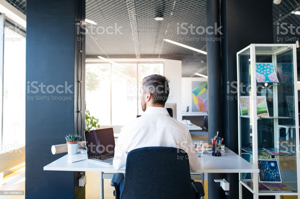 Businessman at the desk with laptop in his office. stock photo