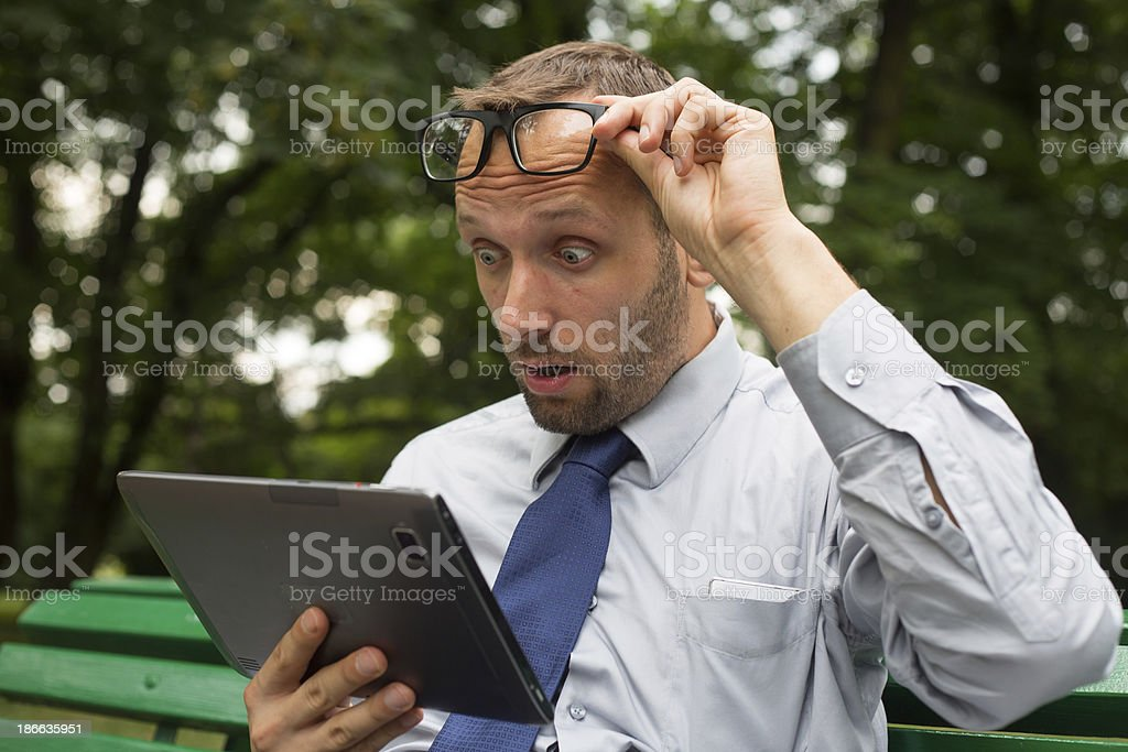 Businessman at the park with tablet sitting on a bench. stock photo