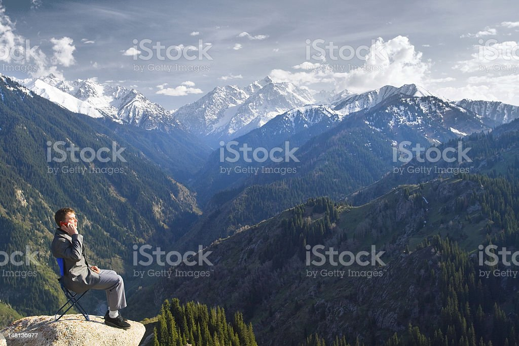 Businessman at the top of mountain is talking by phone stock photo