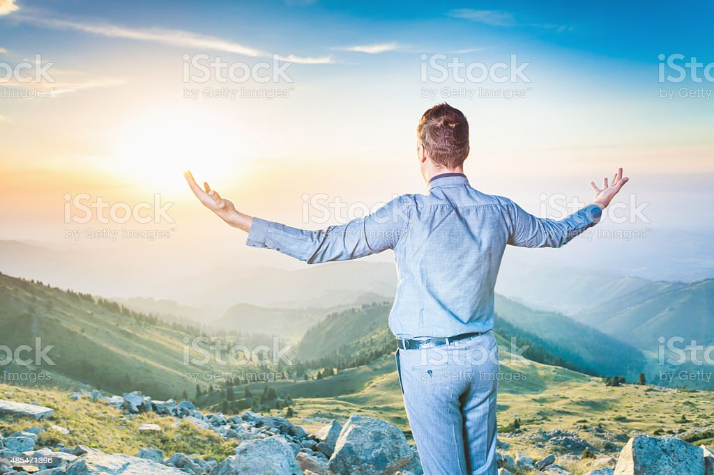 businessman at the top of the mountain sitting and thinking stock photo
