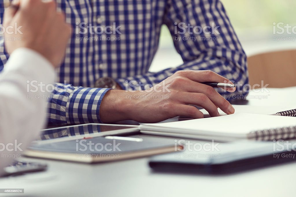 Businessman at work, close up of hands Two businessmen having meeting in a board room in an office, sitting at the conference table and writting notes. Close up of hands, unrecognizable people. 2015 Stock Photo