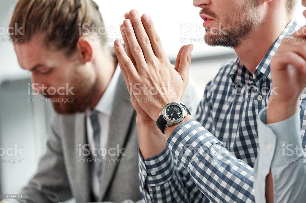 Businessman at work, close up of hands Businessmen having meeting in an office. Focus on man wearing checkered shirt and his hands. 2015 Stock Photo