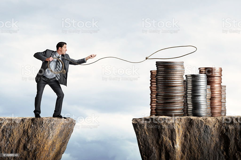 Businessman Attempting To Lasso A Stack Of Coins stock photo
