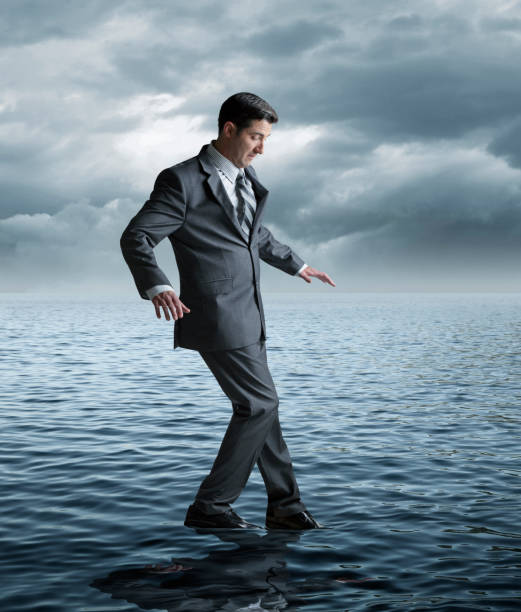 Businessman Attempting To Walk On Water stock photo