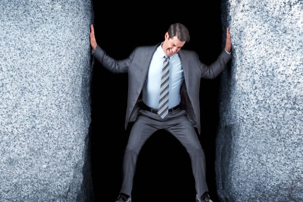 zakenman probeert uit te breiden van de opening tussen de twee grote rotsen - claustrofobie stockfoto's en -beelden