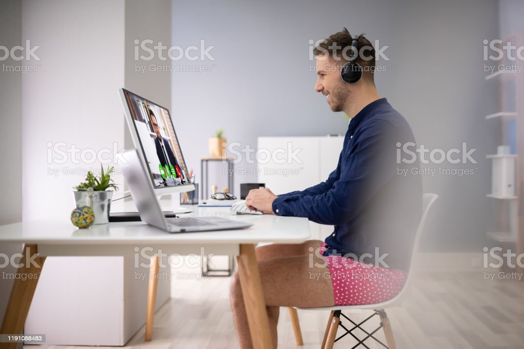 Businessman Attending Video Conference On Computer Young Businessman Using Headphone While Video Conferencing On Computer Adult Stock Photo