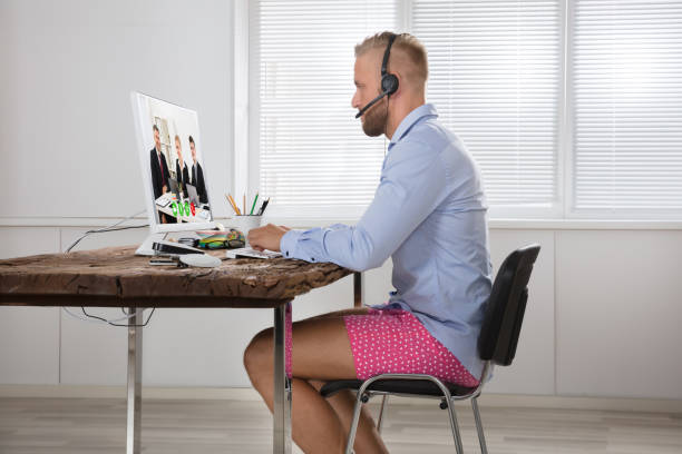 Businessman Attending Video Conference On Computer Businessman Dressed In Shirt And Shorts Having Video Call On Computer In The Home Office shorts stock pictures, royalty-free photos & images