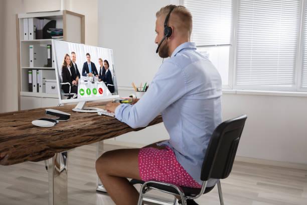 homme d'affaires participant à une conférence vidéo sur ordinateur - homme slip photos et images de collection