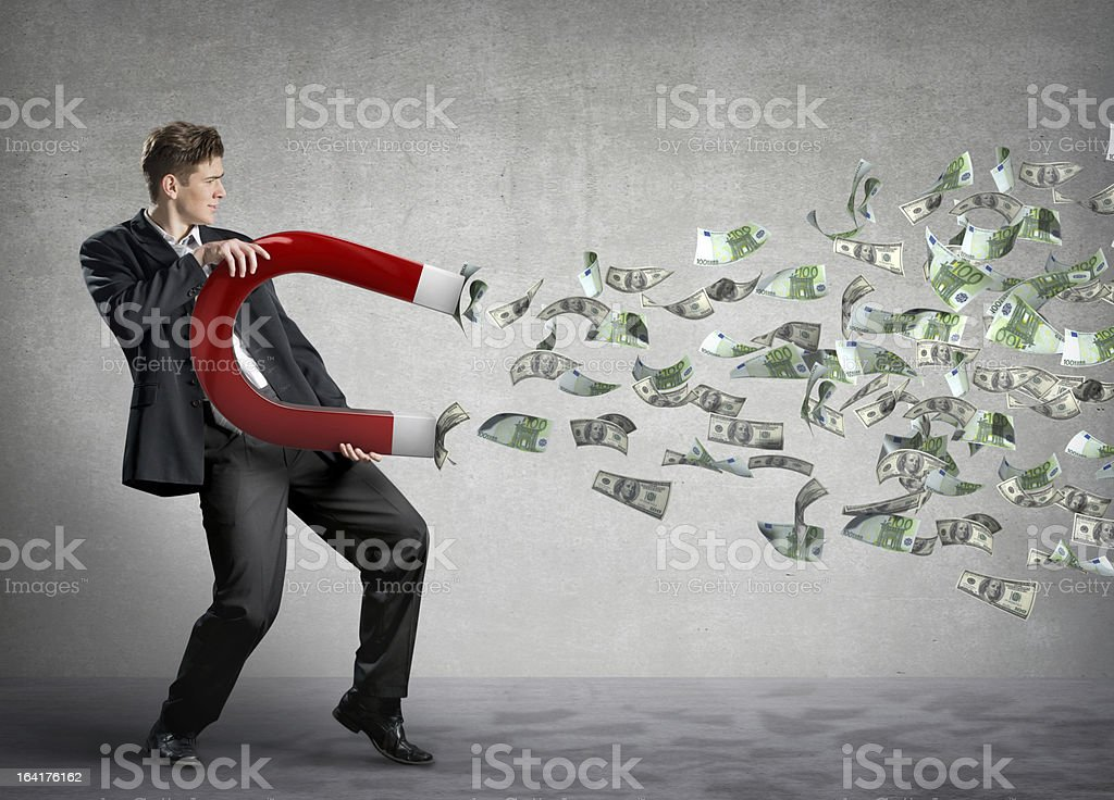 Businessman attracts lots of money with a giant magnet stock photo