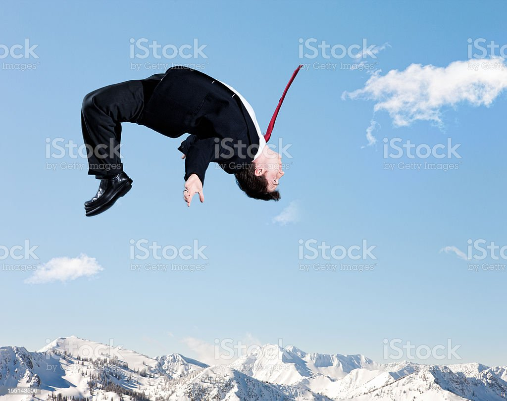 Businessman Backflip in Winter Mountains stock photo