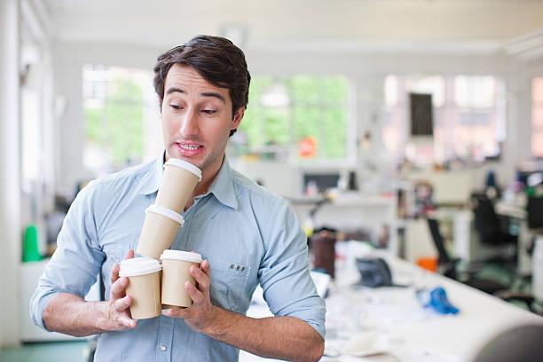 Businessman balancing coffee cups stock photo