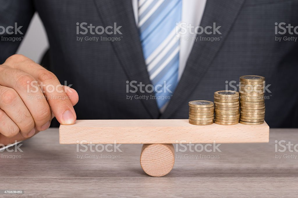 Businessman Balancing Coins On Wooden Seesaw stock photo