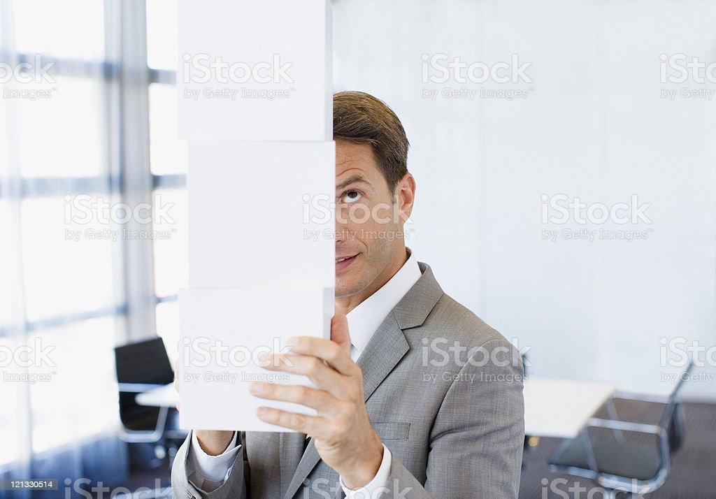Businessman balancing cubes in conference room royalty-free stock photo