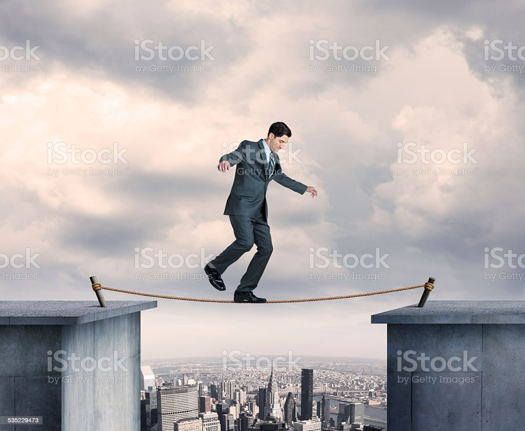 Businessman Balancing On A Tightrope Above Big City stock photo