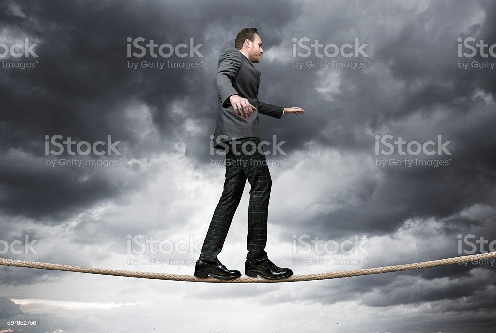 Businessman balancing on tightrope with stormy day stock photo