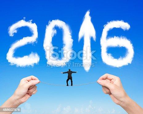 1004788900 istock photo Businessman balancing tightrope woman hands holding 2016 arrow c 488602976