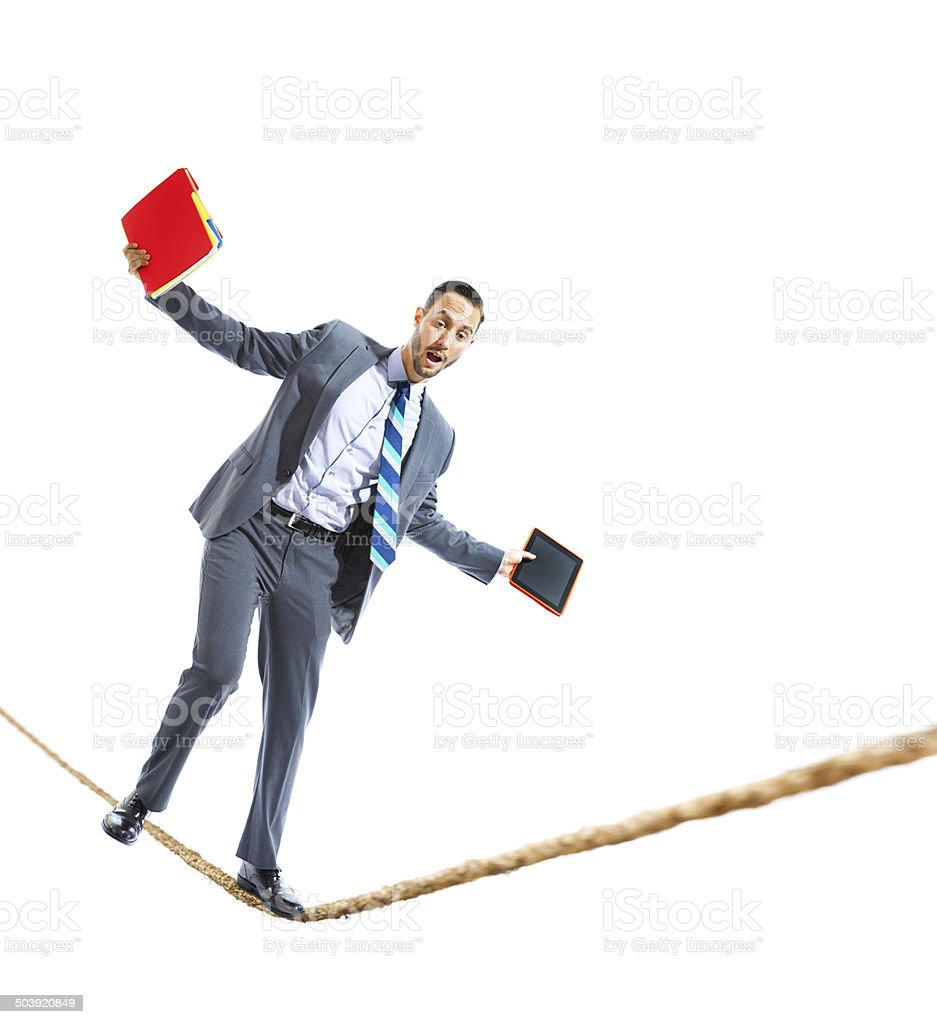 Businessman Balancing Work Life on a Tightrope stock photo