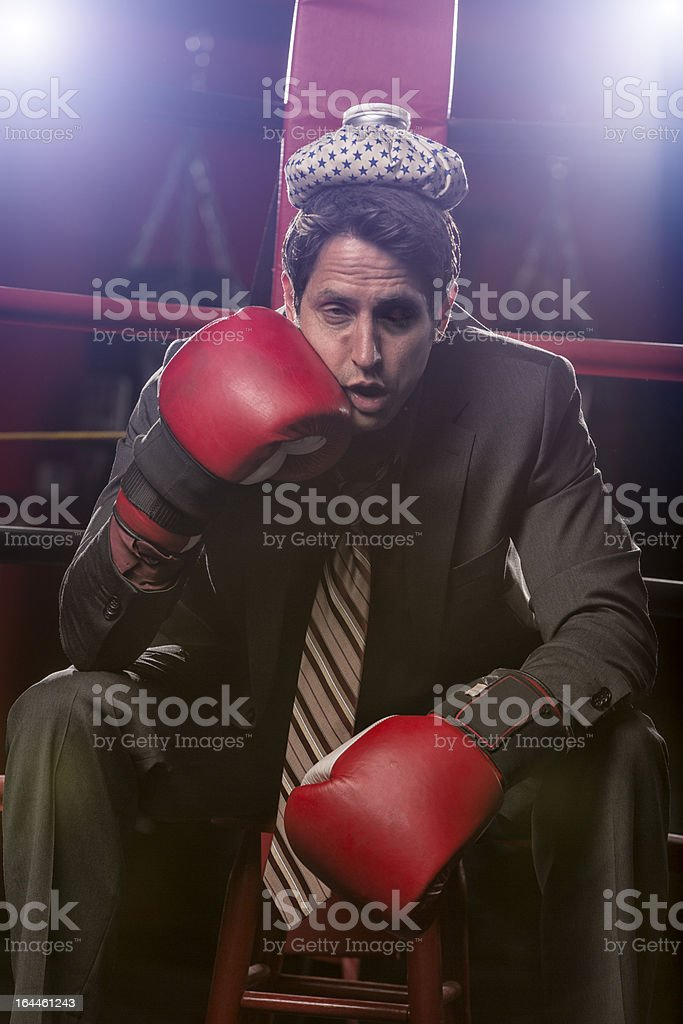 Businessman beat against the ropes with ice pack on head stock photo