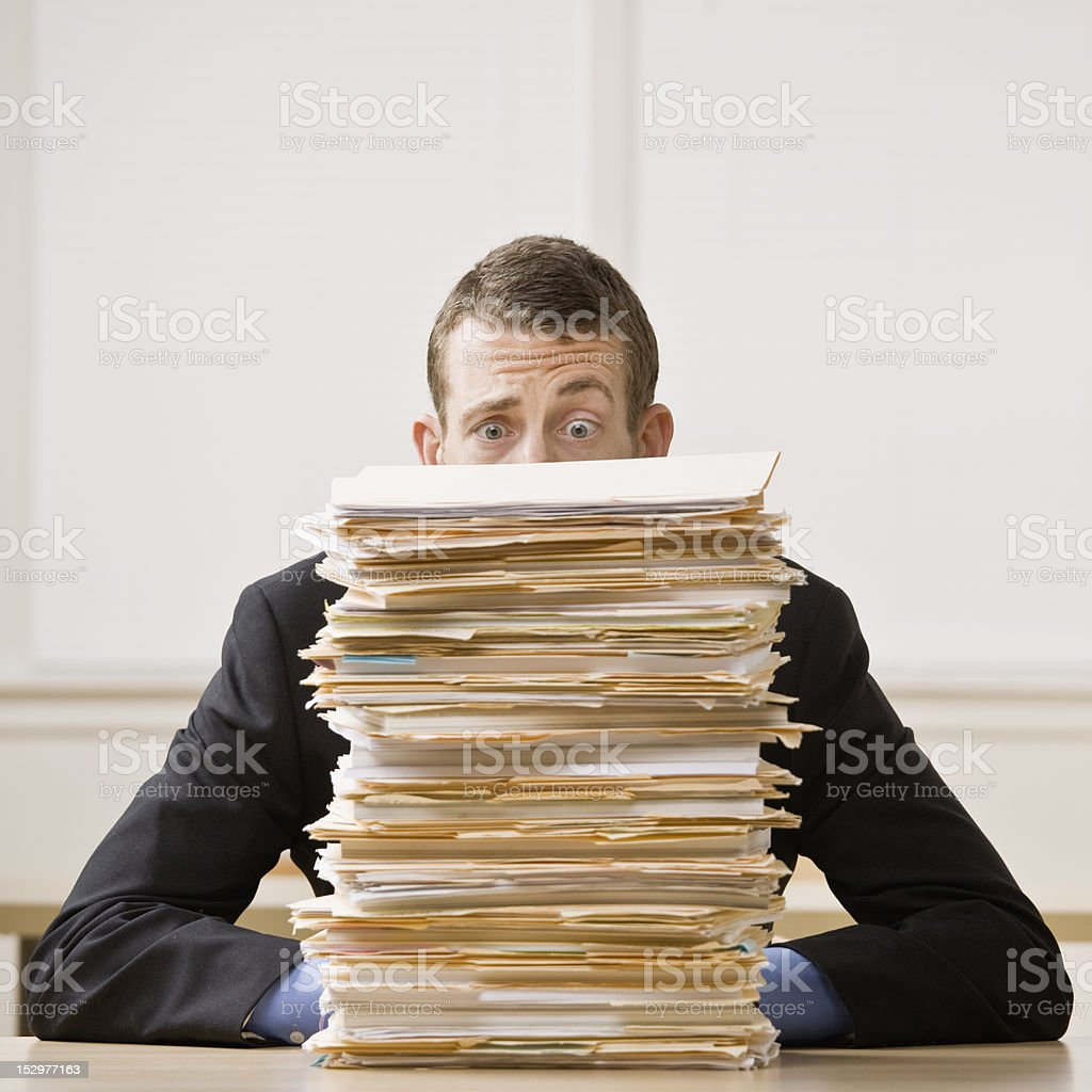 Businessman Behind Stack of File Folders stock photo