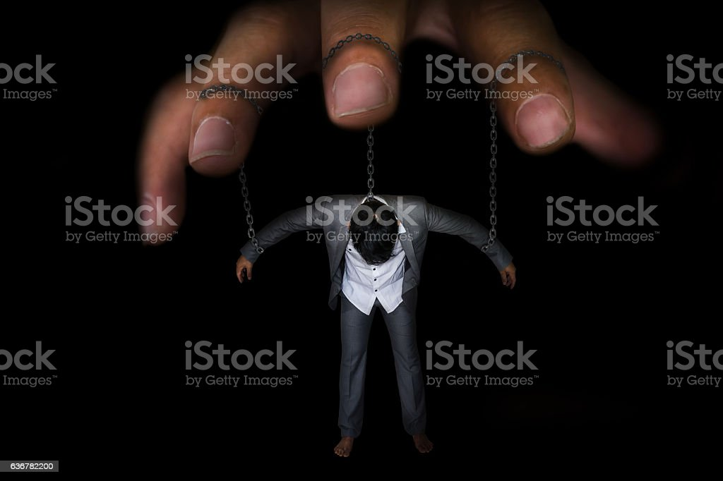 businessman being controlled by puppet master stock photo