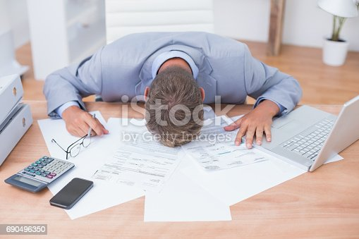 istock Businessman being depressed by accounting 690496350