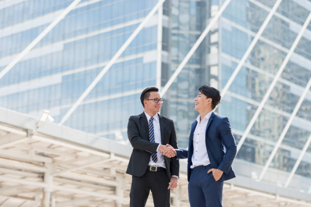 businessman being handshaking. in the background of city building office. Business deals concept stock photo