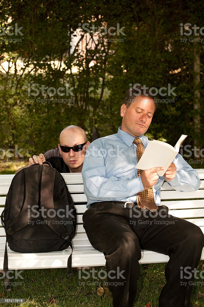 Businessman being robbed in a Park stock photo