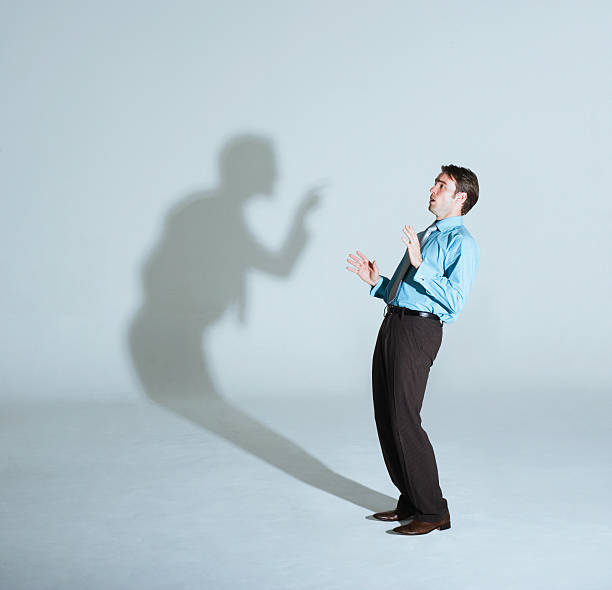Businessman being scolded by his shadow  toned image stock pictures, royalty-free photos & images
