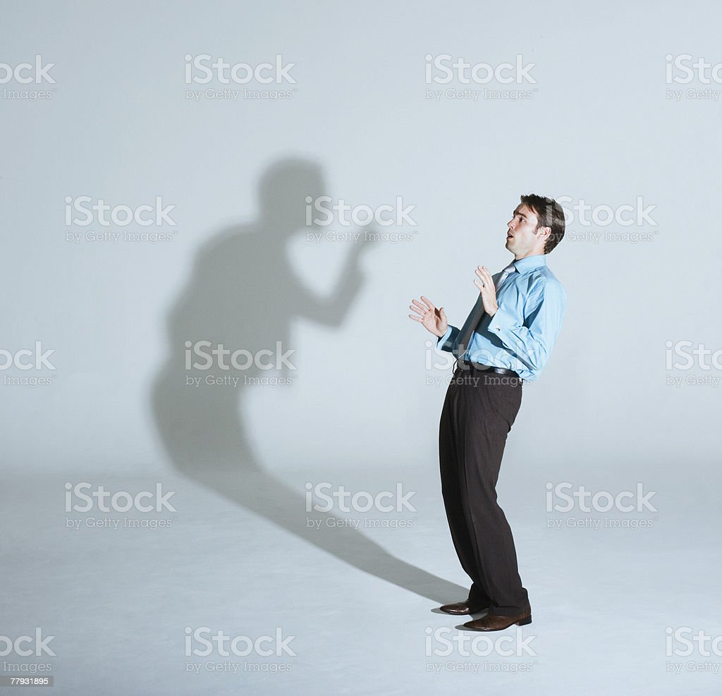 Businessman being scolded by his shadow stock photo