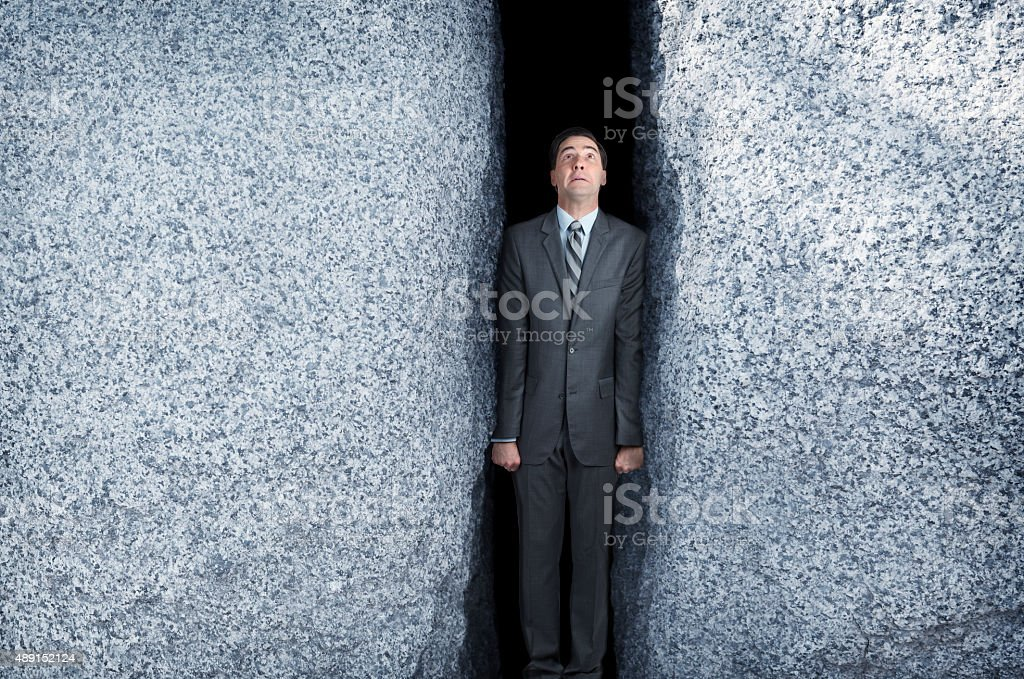 Businessman Being Squeezed By Two Large Granite Rocks stock photo