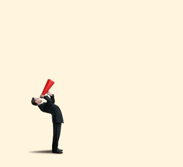 Businessman Bending Over Backwards Shouting Into Megaphone stock photo