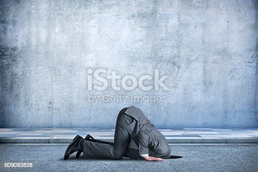 A businessman is bent over in the middle of the street as he buries his head in a hole in the ground.  The concrete wall behind him provides ample room for copy and text.