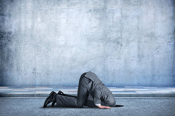Businessman Bent Over With His Head In A Hole - Photo