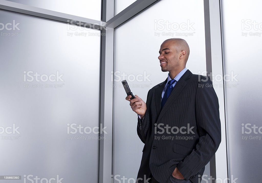 Businessman beside a window looking at cell phone royalty-free stock photo