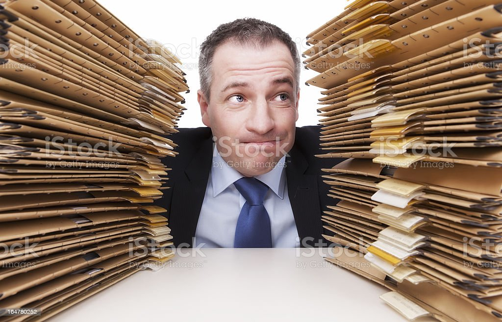 businessman between Stacks of Paperwork royalty-free stock photo