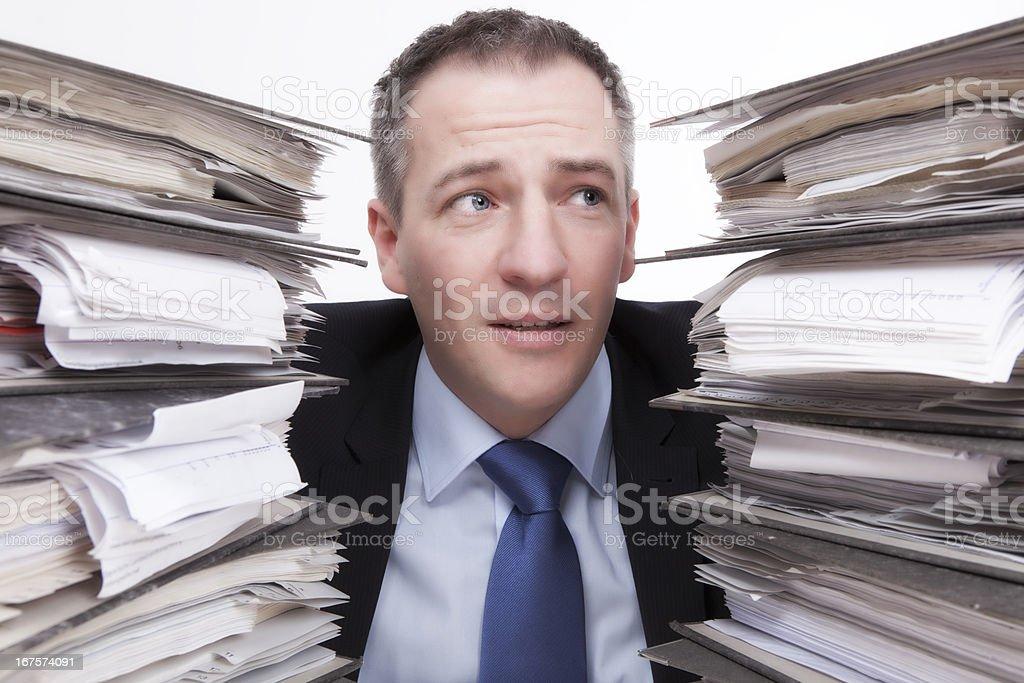 businessman between Stacks of ring binders royalty-free stock photo