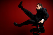 Businessman Blown Away in Office Chair on Red Background