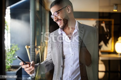 Male executive walking out of a hotel using cell phone. Businessman leaving a hotel lobby and booking an online taxi from his phone.