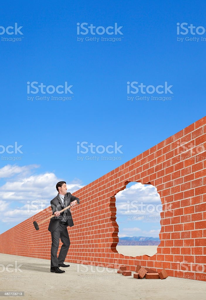 Businessman breaking down a barrier created by brick wall royalty-free stock photo